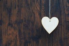 Coeur de contreplaqué accrochant sur la corde à linge Sur le vieux thème de jour en bois background Photos libres de droits