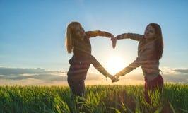 Coeur de coucher du soleil fait par deux filles en été Photographie stock