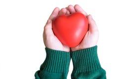 Coeur de couleur rouge de prise de bébé dans le concept de mains, d'amour et de santé de paume Photo stock