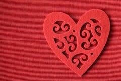 Coeur de coupe-circuit de feutre de rouge sur le fond rouge Photographie stock