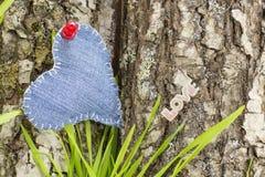 Coeur de denim sur une écorce d'arbre Photographie stock