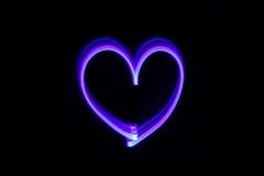 Coeur de dessin avec la lumière dans l'obscurité Photographie stock libre de droits