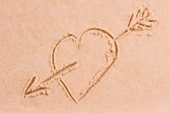 Coeur de dessin avec une flèche sur le sable humide Photographie stock