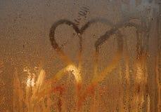 Coeur de dessin avec une flèche sur le vitrail en sueur Un symbole de l'amour Photos libres de droits