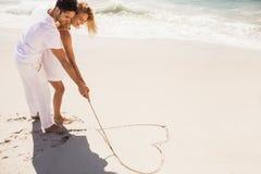 Coeur de dessin de couples sur le sable Image stock