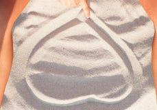 Coeur de dessin de femme au sable Photos libres de droits