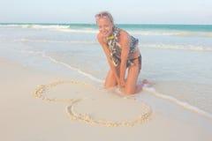 Coeur de dessin de femme sur le sable Image stock