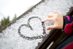 Coeur de dessin de petite fille sur la neige Images libres de droits
