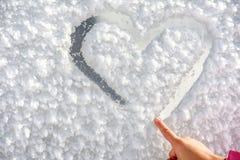 Coeur de dessin de petite fille sur la neige Photos libres de droits