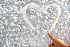 Coeur de dessin de petite fille sur la neige Images stock