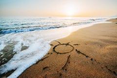 Coeur de dessin sur à sable jaune sur le coucher du soleil fantastique Images libres de droits