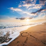 Coeur de dessin sur à sable jaune sur le coucher du soleil fantastique Image libre de droits