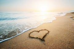 Coeur de dessin sur à sable jaune sur le coucher du soleil fantastique Photo stock