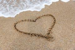 Coeur de dessin sur le sable par la mer Photographie stock libre de droits