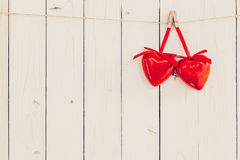 Coeur de deux rouges accrochant sur le bois blanc avec l'espace pour Valentine et Image stock