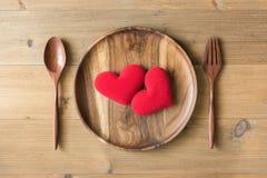 Coeur de deux rouges dans le plat en bois Images libres de droits