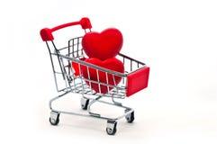 Coeur de deux rouges dans un caddie d'isolement sur le fond blanc Photo stock
