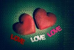 Coeur de deux rouges et AMOUR des trois textes sur le fond de texture Photographie stock libre de droits