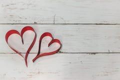 Coeur de deux rouges fait en ruban sur un fond en bois utilisant comme le lov Photos libres de droits