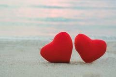 Coeur de deux rouges sur la plage de sable Images libres de droits