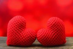 Coeur de deux rouges sur la table en bois et le fond rouge Photo stock