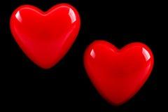 Coeur de deux rouges sur le fond noir Photos libres de droits