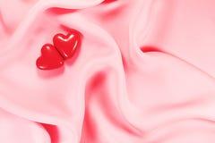 Coeur de deux rouges sur le rose Photographie stock