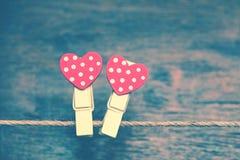 Coeur de deux rouges sur un fond de bois Coeur créatif - pinces à linge accrochant sur une corde Photos libres de droits
