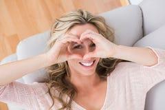 Coeur de fabrication blond de sourire avec ses mains Photos stock
