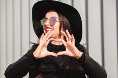 Coeur de fabrication modèle de belle brune avec ses doigts dans le jour ensoleillé Photos libres de droits