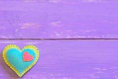 Coeur de feutre d'isolement sur un fond en bois pourpre avec l'espace de copie pour le texte Valentine de feutre Symbole de jour  Images stock
