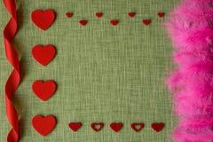Coeur de feutre et plumes d'oiseau teintes sur le fond de tissu Photographie stock libre de droits
