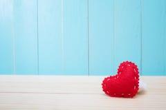 Coeur de feutre ouvré par main sur le fond bleu Photographie stock