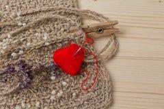 Coeur de fil en tissu et de flowerson sec sur le fond en bois Image stock