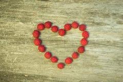 Coeur de framboise sur le fond de conseil en bois images libres de droits