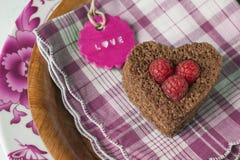 Coeur de gâteau et de framboises, carte rouge Image stock