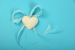 Coeur de gypse avec des fleurs et ruban sur le fond bleu Photo libre de droits