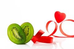 Coeur de kiwi et rubans en forme de coeur et rouges sur un fond blanc Photographie stock