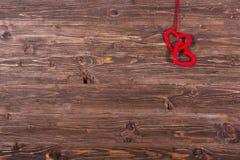 Coeur de laine de l'amour deux accrochant sur le fond en bois Photo stock