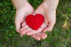 Coeur de laine rouge dans une main humaine, jour de valentines, amour Images stock