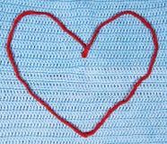 Coeur de laine rouge de ficelle sur le tissu à crochet Images stock