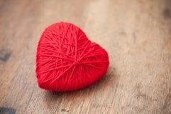 coeur de laine rouge sur le fond en bois de table Photographie stock