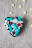 Coeur de médicament coloré et pilules ci-dessus sur le fond en bois gris Copiez l'espace Vue supérieure, cadre Calmants, comprimé Photographie stock