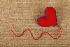 Coeur de métier de feutre de rouge au-dessus de fin de toile  Photographie stock