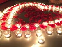 Coeur de pétale de rose avec la bougie la nuit Photos stock