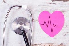 Coeur de papier avec la ligne de cardiogramme et de stéthoscope sur le concept en bois de fond, de médecine et de soins de santé Photo stock