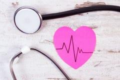 Coeur de papier avec la ligne de cardiogramme et de stéthoscope sur le concept en bois de fond, de médecine et de soins de santé Images stock