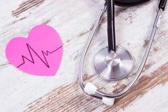 Coeur de papier avec la ligne de cardiogramme et de stéthoscope sur le concept en bois de fond, de médecine et de soins de santé Image libre de droits