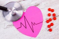 Coeur de papier avec la ligne de cardiogramme, pilules de stéthoscope et de supplément, médecine et concept de soins de santé Photographie stock libre de droits