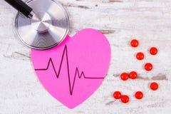 Coeur de papier avec la ligne de cardiogramme, pilules de stéthoscope et de supplément, médecine et concept de soins de santé Image libre de droits